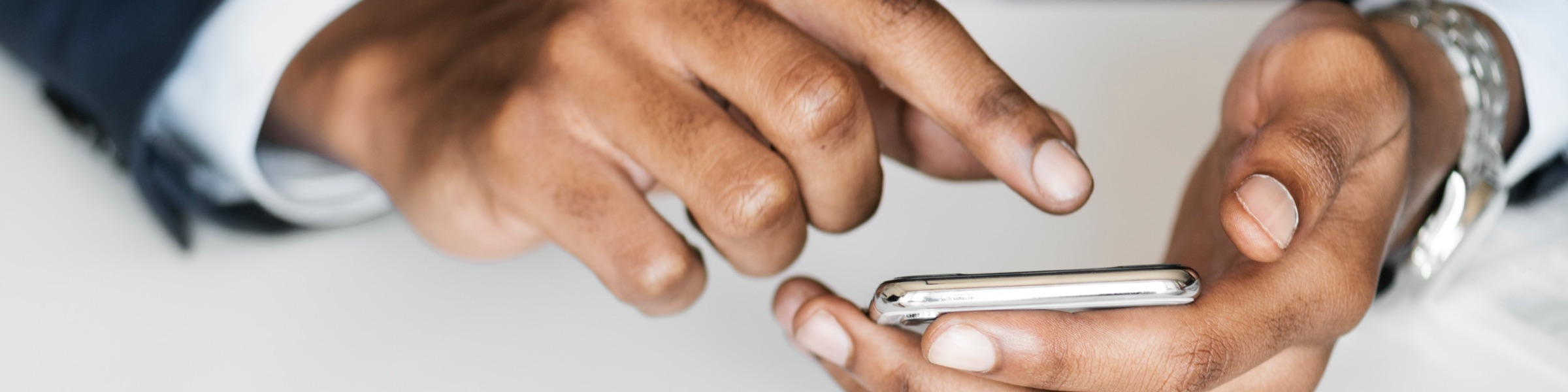 a close up of a business man's hands while he is using his phone to text someone