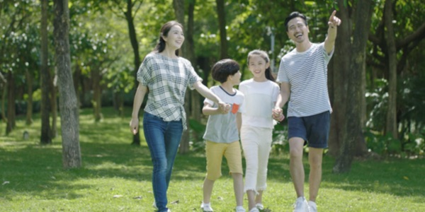 a picture of Korean family, a mother, father, and two kids walking through a park holding hands